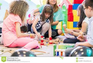 dedicated-young-female-kindergarten-teacher-holding-pre-school-shy-girl-watching-children-playtime-wooden-toy-116066076[1]